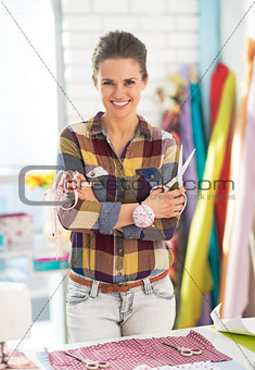 Portrait of smiling tailor woman with scissors and measuring tap