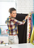 Portrait of happy tailor woman working with fabric in studio