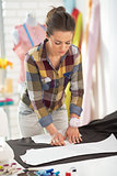 Happy tailor woman working with fabric in studio