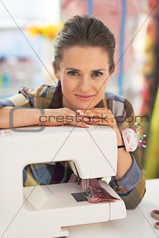 Portrait of happy tailor woman with sewing machine
