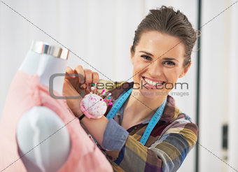 Portrait of smiling tailor woman working in studio