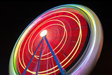 Beautiful Long exposure picture of a ferris wheel rotating, vivid colors.