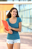 Happy student teenager girl walking out of the school