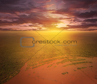 Flight above Parana river and tropical forests at sunset time.