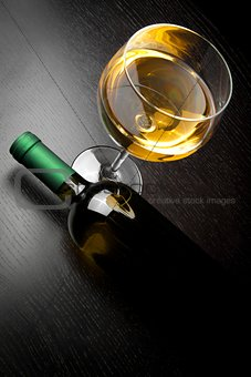 top of view of white wine glass near bottle