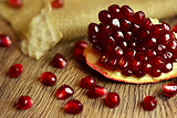 Raw pomegranate with seeds on wood