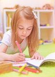 Preschooler girl painting in daycare