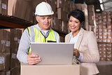 Warehouse worker and manager looking at laptop