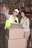 Warehouse worker and manager using laptop