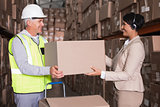 Warehouse worker and manager passing a box