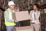 Warehouse worker holding box with manager on a call