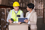 Warehouse worker scanning box with manager