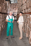 Warehouse worker and manager smiling at camera