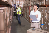 Pretty warehouse manager checking inventory