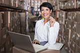 Pretty warehouse manager smiling at camera using laptop