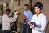 Pretty warehouse manager using tablet during busy period