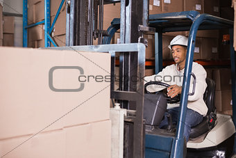 Forklift driver operating machine with boxes on it
