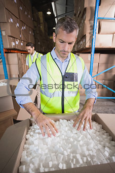 Warehouse worker in yellow vest preparing a shipment