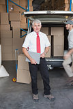 Warehouse manager smiling at camera with delivery in background