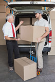Warehouse manager and delivery driver talking beside van