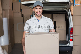 Delivery driver smiling at camera holding box