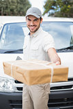 Delivery driver smiling at camera by his van offering parcel