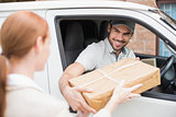 Delivery driver handing parcel to customer in his van
