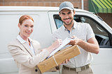 Delivery driver handing parcel to customer outside van