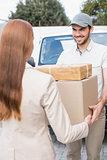 Delivery driver passing parcels to happy customer