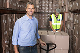 Warehouse manager smiling at camera with trolley