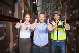Warehouse team smiling at camera showing thumbs up