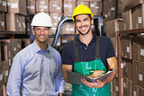 Warehouse manager and foreman smiling at camera