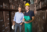 Warehouse manager smiling at camera with worker