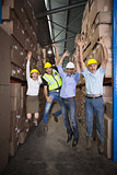 Warehouse team smiling at camera jumping and cheering