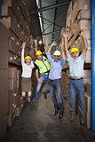Warehouse team smiling at camera jumping and cheering