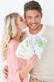Woman kissing man as she holds banknotes