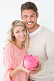 Portrait of attractive young couple holding piggybank