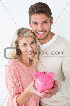 Attractive young couple holding piggybank