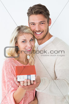 Attractive young couple holding mini house