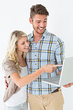 Happy attractive young couple using laptop