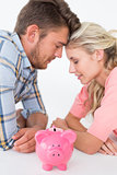 Attractive young couple with piggybank