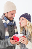 Attractive couple in warm clothing holding gift