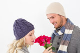 Attractive couple in warm clothing holding flowers