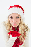 Young woman wearing santa hat as she blows kiss