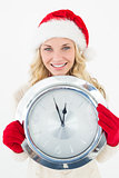 Portrait of attractive santa woman holding clock