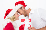 Attractive couple wearing santa hats with gift