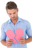 Young man holding broken heart
