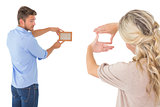 Rear view of young couple hanging up picture frame