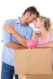 Couple with piggybank over cardboard box