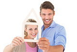 Attractive young couple looking through house outline